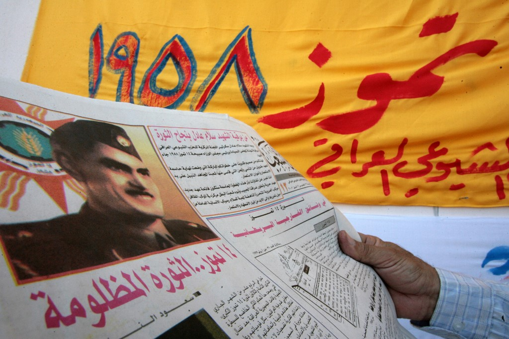 An Iraqi reads a communist party newspaper, 14 July 2007 in Baghdad, bearing a front page picture of General Abd al-Karim Qassim during a ceremony to commemorate the 1958 coup. (AFP)