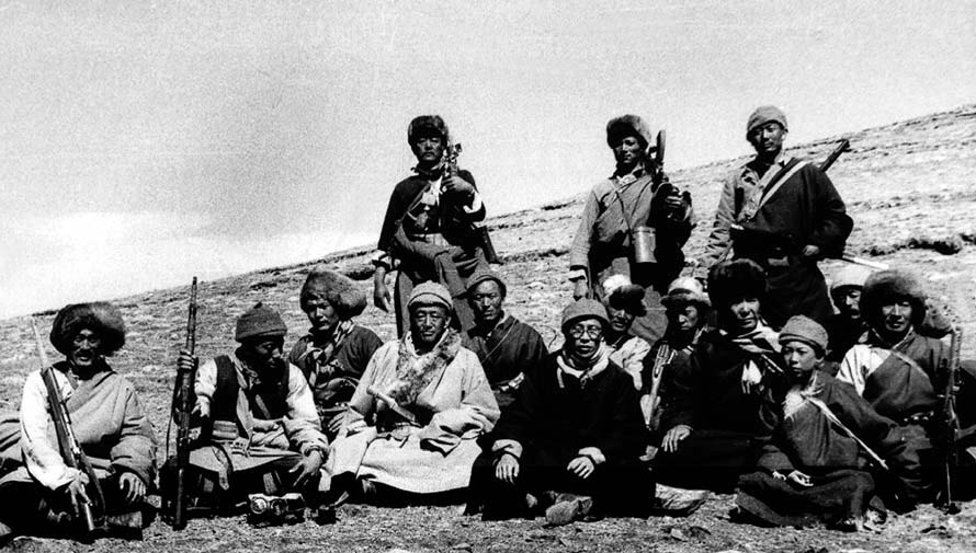 "The Dalai Lama (front right center, in black, wearing glasses) poses with his armed guerrilla escort as he flees Tibet after having instigated a militarily futile ""uprising"" of monks against the revolutionary Chinese government's overthrow of his feudalist theocratic rule. Date unknown."